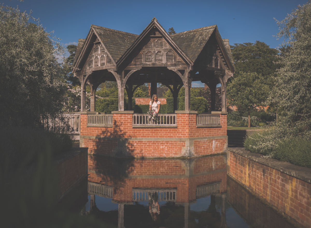 Bride in the centre of pavilion surrounded by reflecting water.
