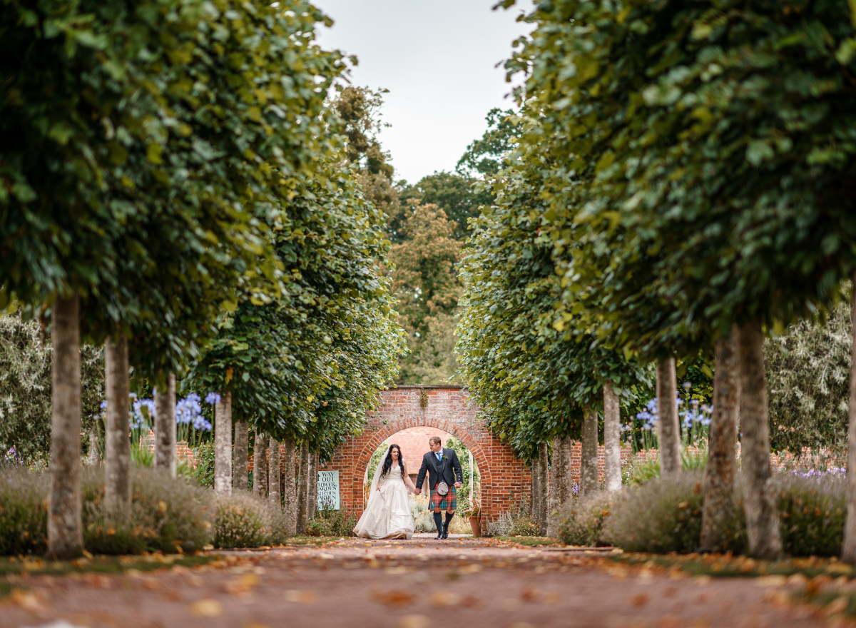 Couple walking down avenue of trees