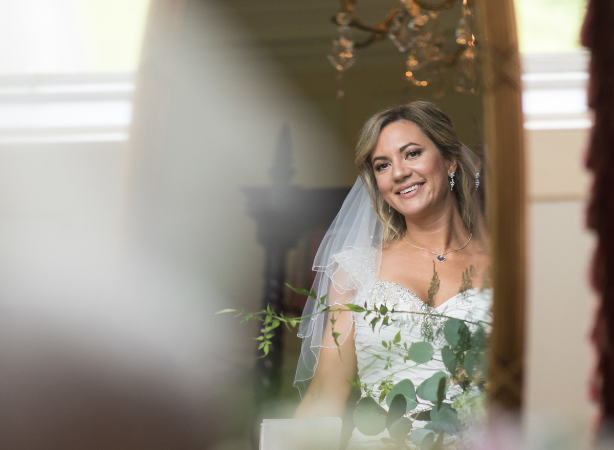 Bride's reflection in mirror with chandelier and flowers