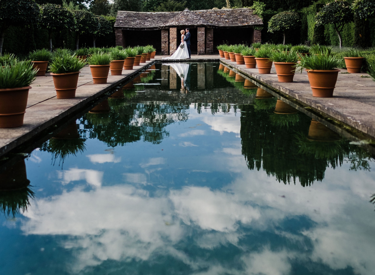 A rectangular pool of water reflecting the sky, at the end a bride and groom