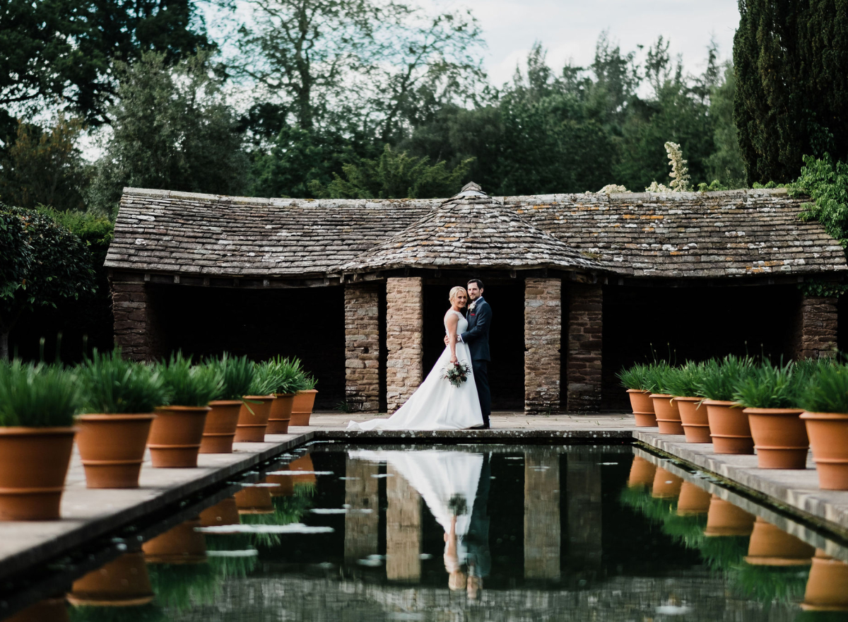 Wedding couple in front of hut with canal in foreground.
