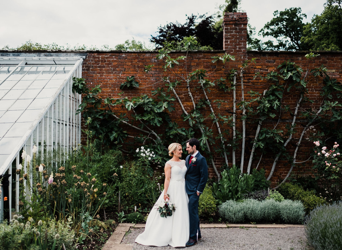 A bride and groom in a walled garden.