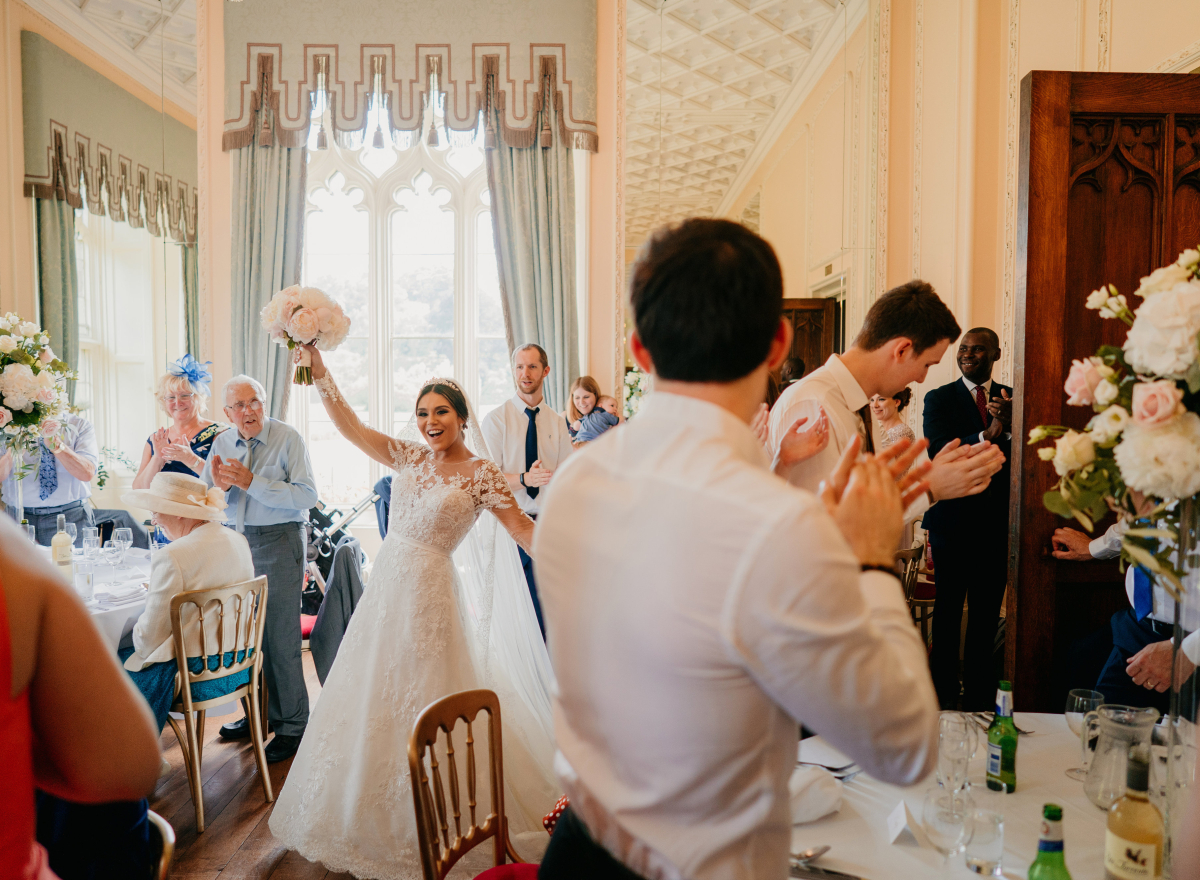 Bride raising bouquet in celebration surrounded by guests in ballroom